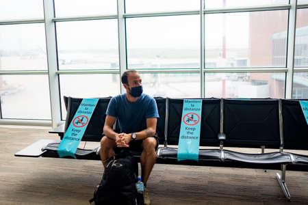 Barcelona, Spain - 20 august 2020: young man sit alone inside airport with face mask and social distancing sign, traveling in the time of corona virus Editorial
