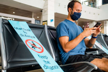 Barcelona, Spain - 20 august 2020: young man inside airport with face mask and social distancing sign, traveling in the time of corona virus Editorial
