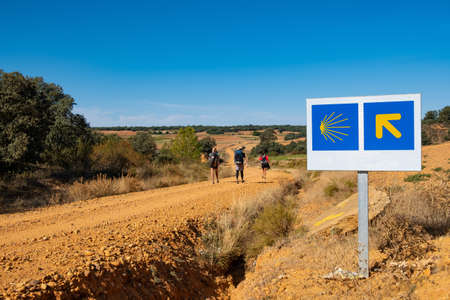Pilgrims with backpack walk along Saint James way, also known as Camino de Santiago, on a sunny day in the countryside, with arrow and seashell pointing the way
