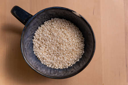 top view of blue bowl of white uncooked raw rice on wooden table. rice is a staple food and a base for the nutrition and diet of a lot of people