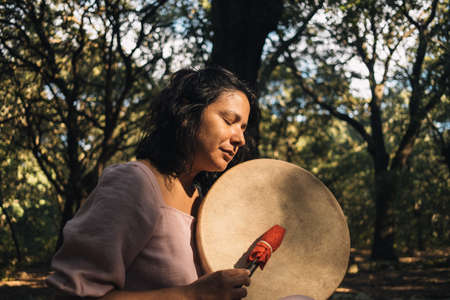 young woman playing tambour in the woods in nature with incense. mystic woman doing ritual and ceremony . musician woman playing tribal drums