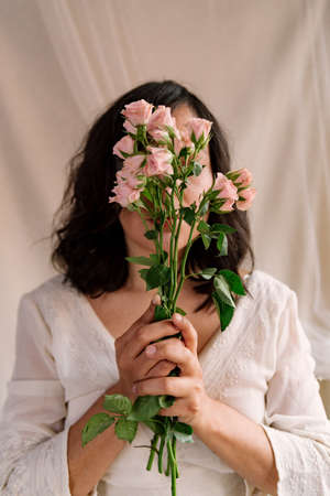 portrait of smiling young woman with pink roses and natural look. close up during springtime. serious expression with eyes wide open. concept of happy spring season