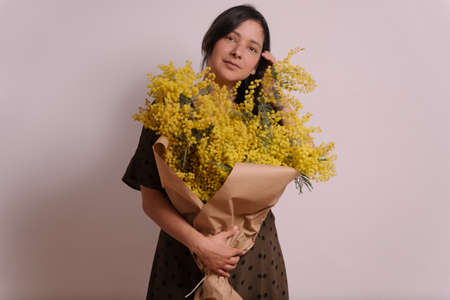 womans day celebration with mimosa. portrait of young woman holding yellow mimosa flowers bouquet on white background smiling with casual clothes.