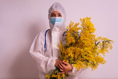 international women's day celebration during covid pandemic concept. young nurse holding yellow mimosa flowers to celebrate 8 march in hospital with face mask