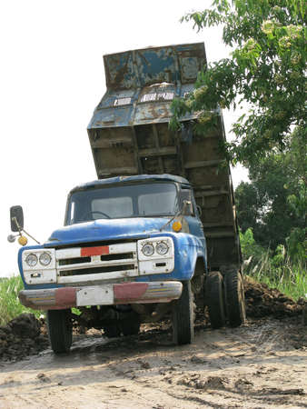 dumping: Old and rusty blue dump truck is dumping soil