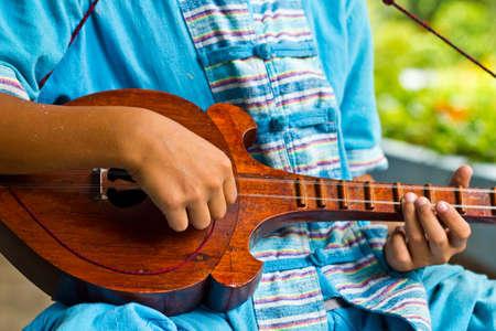 thai musical instrument: the boy plays a local Thai music instrument