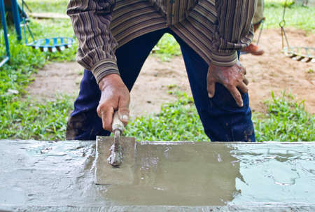 Mason building a screed coat cement in his site photo