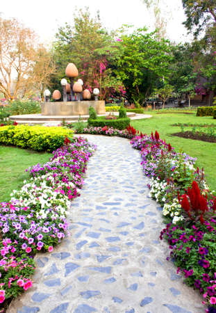 concrete walkway in a lush green park Stock Photo