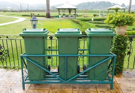 tripple: tripple green plastic bin in the park