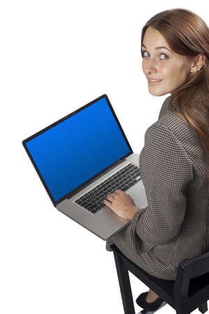 Smiling happy woman sitting and using laptop - High angle view Stock Photo