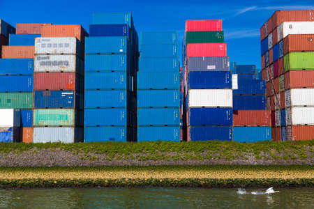 tonnage: Swan taking off against containers stacked in Port of Rotterdam, Netherlands Stock Photo