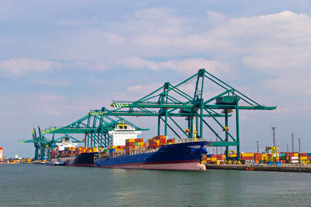 dockside: Huge container ships being loaded with cranes in Antwerp container terminal
