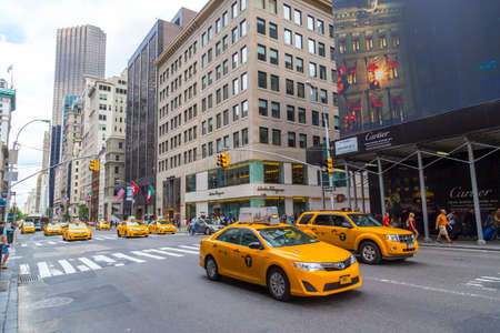 Yellow taxi cabs ride on 5th Avenue in New York City, USA.