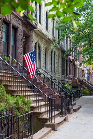 Stairway with an American flag by the brownstone houses in urban residential neighborhood of Brooklyn, NYC.