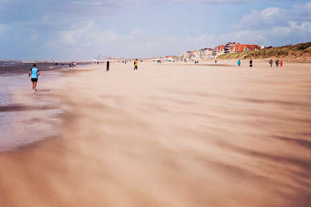 People walking and jogging along the beach against strong winds carrying sand at North Sea coast, Belgium
