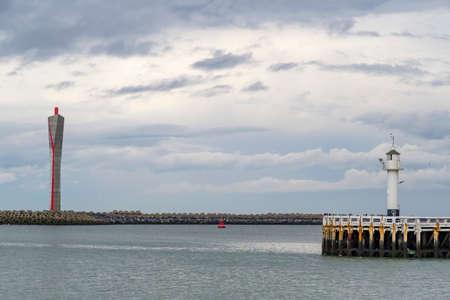 longitudinal: Old-fashioned sea lighthouse and modern radar tower on the longitudinal embankment along the North Sea coast at Ostend, Belgium
