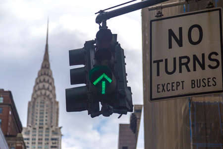 No turns road sign with green traffic light and the Chrysler building in background