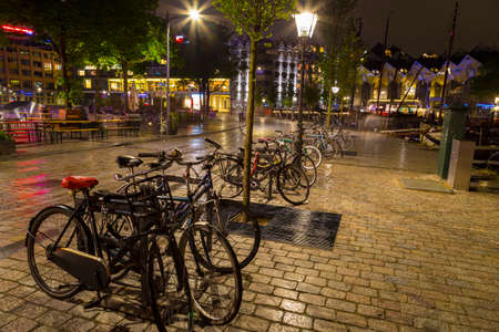 city park boat house: Bicycles parked at night in historical part of Rotterdam, Netherlands
