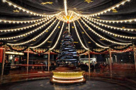 Blurry light background with long exposure of carousel rotating during christmas fair in Cologne, Germany