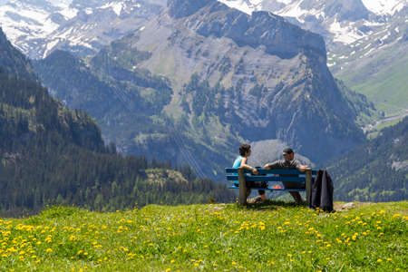 the bernese oberland: Couple sitting on bench observing amazing view of Swiss Alps and meadows near Oeschinensee Oeschinen lake, on Bernese Oberland, Switzerland Editorial