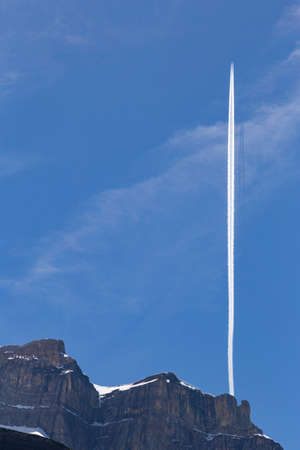 bernese oberland: Vertical contrail of an airplane over a snowy mountain peak near Oeschinensee Oeschinen lake, on Bernese Oberland, Switzerland
