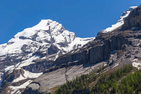 the bernese oberland: View of mountain rocks and ice-capped Swiss Alps near Oeschinensee Oeschinen lake, on Bernese Oberland, Switzerland Stock Photo