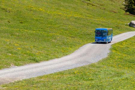 oberland: Tourist bus driving along trekking path near Oeschinensee Oeschinen lake, on Bernese Oberland, Switzerland