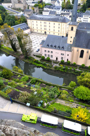 arial view: Arial view of Grund district of Luxembourg City seen with Neumuenster Abbey, Alzette river and green touristic train Editorial