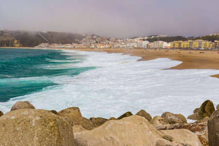 crushing: Crushing emerald waves on sandy beach in Nazare, Portugal Editorial