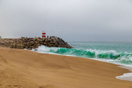 crushing: Large ocean waves crushing pier with lighthouse in Nazare, Portugal Stock Photo