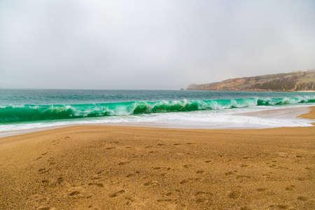 crushing: Crushing emerald waves on sandy beach in Nazare, Portugal Stock Photo