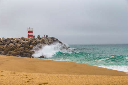 crushing: Large ocean waves crushing pier with lighthouse in Nazare, Portugal Editorial