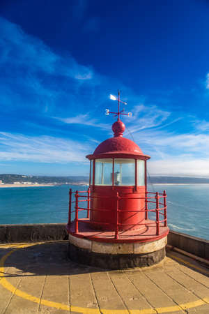Closeup of a lighthouse lamp room on blue sky background in Nazare, Portugal Stock Photo