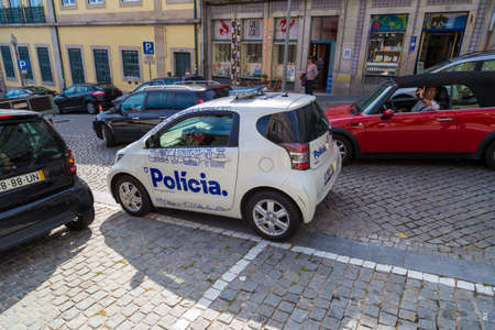 law of portugal: PORTO, PORTUGAL - 12 SEPTEMBER 2016: Small white police car parked on street of Porto, Portugal