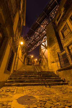 Night shot of city street and Dom Luis I bridge above houses in Porto, Portugal