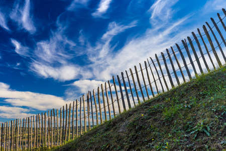 picket green: Old wooden fence on dramatic blue sky background