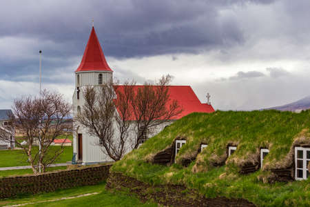 Red rooed church in Glaumbaer village and small cottages with turf roofs in Northern Iceland