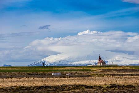 View of a church along Snæfellsnesvegur road seen against Snaefellsjoekull glacier Stok Fotoğraf