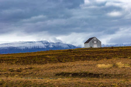 Typical Icelandic landscape with snowy mountains against cloudy sky near Husavik, Northern Iceland