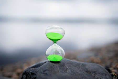 Modern Hourglass with green background -- sand trickling through the bulbs of a crystal sand glass. every second counts. symbol of time. countdown.