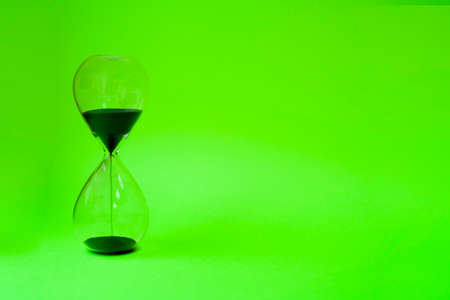 black hourglass on green background close-up Stock fotó