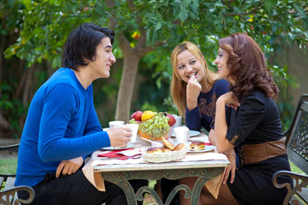 Three young students sitting at an outdoor restaurant table enjoying a cup of coffee and fruit while chatting photo