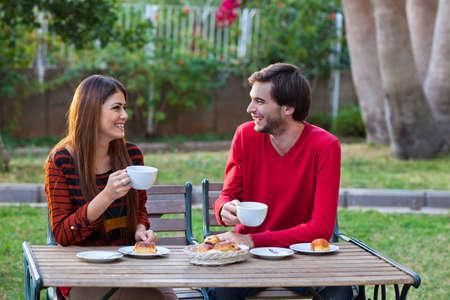 Happy smiling couple having lunch in garden photo