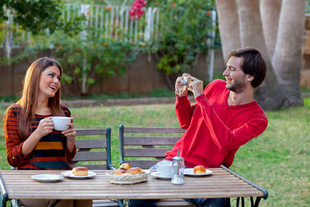 compact camera: Smiling man photographing his girlfriend or wife while enjoying coffee and cakes at an outdoor cafe