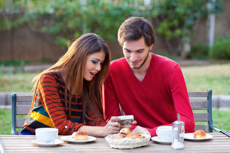 exclaim: Young couple having coffee and pastries at an outdoor table exclaim over a photograph that they are viewing on the back of a compact digital camera
