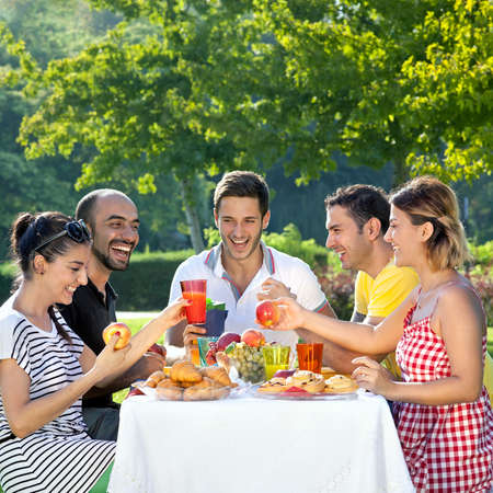 Multiethnic friends sharing an enjoyable meal seated at a table outdoors in the garden laughing and joking together Stock Photo