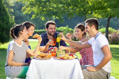 personas comiendo: Amigos disfrutando de un picnic relajante sentados juntos riendo y charlando en una mesa en un parque de vegetación exuberante