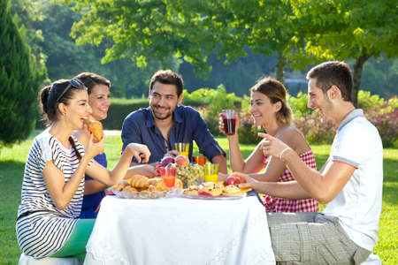 extended family: Group of five adult friends enjoying a healthy outdoor meal sitting together at a table in a lush green garden laughing and joking