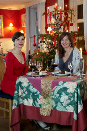 Two girlfriends having a christmas dinner in a restaurant photo