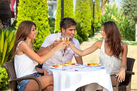 Three young friends, two women and a man, toasting while having lunch outdoors photo